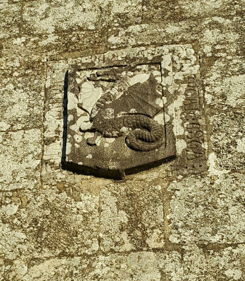 Escudo con dragón alado en la fachada de la iglesia de Santa María de Marrozos